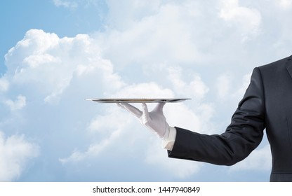 Waiter holding empty silver tray over blue sky