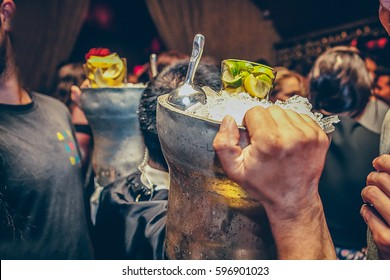 A waiter is holding ice buckets with mojito on his shoulders
