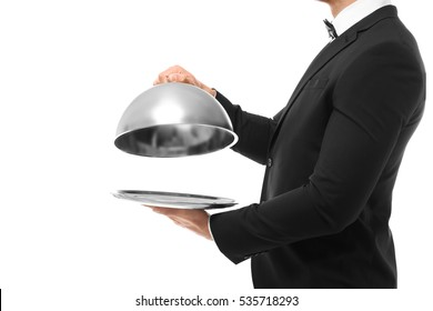 Waiter holding metal tray with cover on white background, close up view