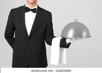 Waiter holding metal tray with lid on light background