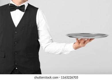 Waiter holding metal tray on light background