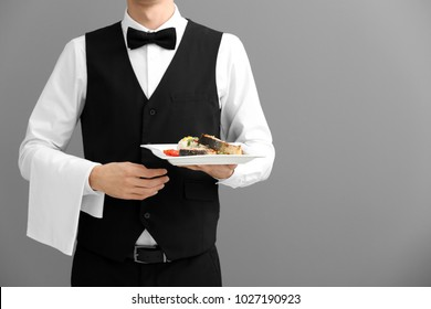 Waiter holding plate with fish and rice on gray background