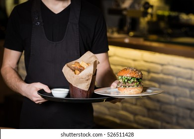 Waiter holding the plate with hamburger and chips in the restaurant with white bricks.