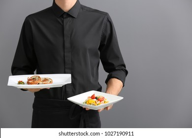 Waiter holding plates with dishes on gray background