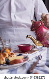 A waiter holding tea pot pouring tea with Blueberry apple waffle set on a dish ready to serve.