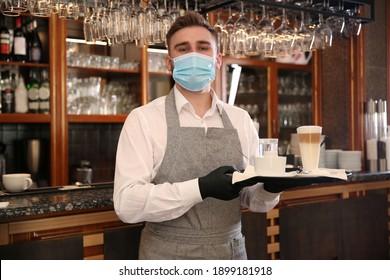 Waiter holding tray with beverages in restaurant. Catering during coronavirus quarantine