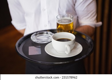 Waiter holding tray with coffee cup and pint of beer in a bar
