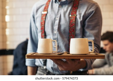 Waiter holding a tray with coffees in the bar.
