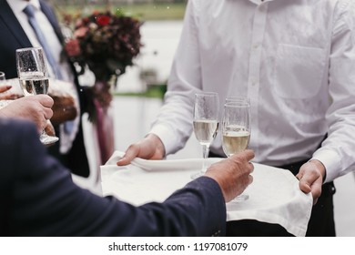 Waiter holding tray with glasses of champagne and serving them for toasts wedding reception. People cheering with alcohol drinks at party outdoors. Luxury Christmas feast