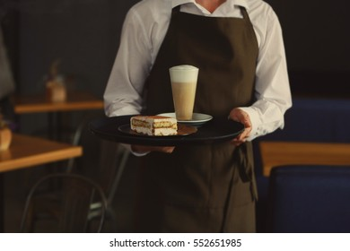 Waiter holding tray with tasty dessert and chocolate drink, close up view