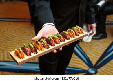 a waiter holding a wooden platter full of taco appetizers - wedding catering series