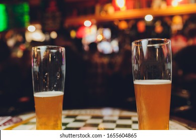 waiter holds glasses of beer in hands in a bar or pub. Beer glasses.