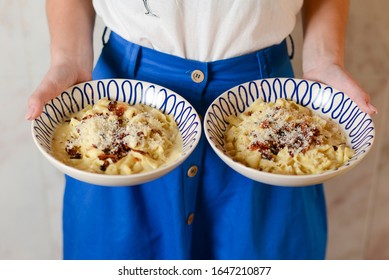 A waiter holds two plates of tasty food. Italian cuisine in restaurant, Pasta with sauce and parmesan cheese and vegetables. Traditional Italian cuisine. Waiter in white and blue uniform.
