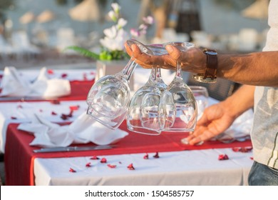 The waiter holds wine glasses in his hand and sets the table in a restaurant . Nice dining table set with arranged silverware and napkins for dinner, Turkey. Close up