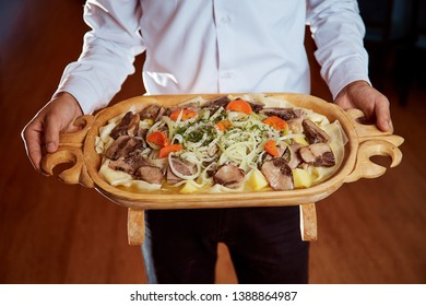 The waiter keeps a tasty Kazakh national dish beshbarmak in a wooden plate with kazy, flour tortillas, onions and potatoes