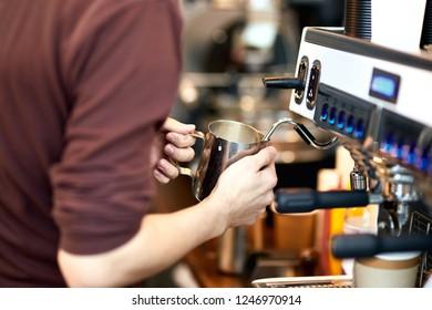 Waiter is making coffee on a modern coffee machine