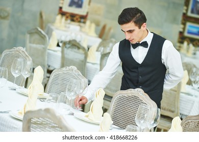 waiter man serving banquet table at restaurant