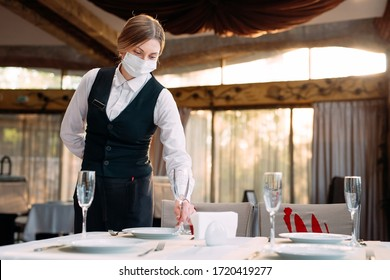 Photo of A waiter in a medical protective mask serves the table in the restaurant