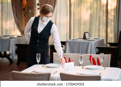 A waiter in a medical protective mask serves the table in the restaurant