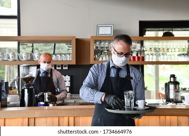 waiter in a medical protective mask serves  the coffee in restaurant durin coronavirus pandemic representing new normal concept - Shutterstock ID 1734664976