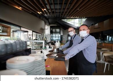 Kellner in einer medizinischen Schutzmaske serviert den Kaffee im Restaurant während der Coronavirus-Pandemie, die ein neues normales Konzept darstellt