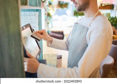 Waiter of modern cafe or restaurant entering payment information after serving client