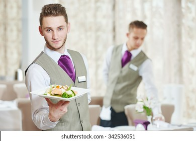 Waiter occupation. Young man with food on dishes servicing in restaurant