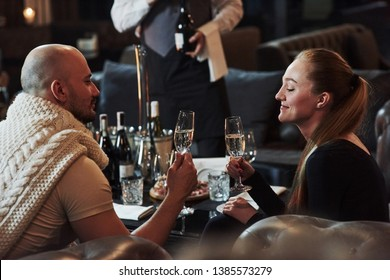 Waiter opens bottle of wine. Girl with her boyfriend have nice evening at beautiful restaurant.