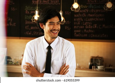 "A waiter is a person who ""waits"" on tables, often at a restaurant or cafe. They will take orders and delivers food to customers. He is standing at counter."
