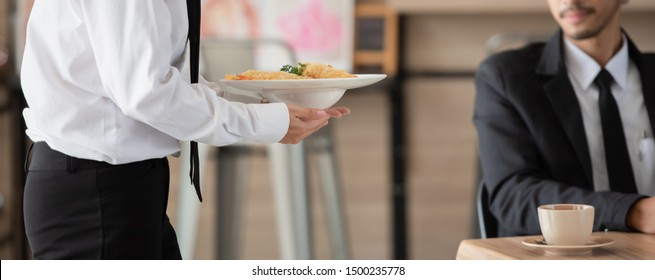 Waiter with plate of food in hand serving at table at restaurant, health care concept.
