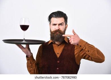 Waiter points at tray and glass of red wine. Barman with serious face holds alcoholic drink. Service and restaurant catering concept. Man with beard and mustache holds alcohol on white background
