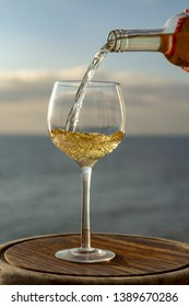 Waiter pouring aperitif cold white wine in glasses on outdoor tessace witn sea view in sunny day