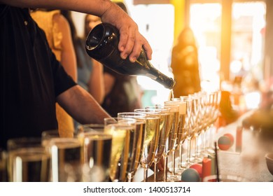 Waiter pouring champagne into glasses on party event in the bar