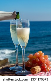Waiter pouring Champagne, prosecco or cava in two glasses on outside terrace with sea view  close up