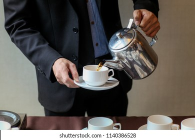 Waiter Pouring Coffee into a white cup.Ready to serve