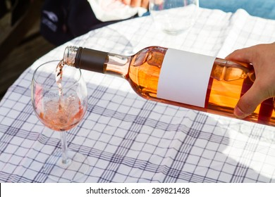 Waiter pouring a glas of rose wine