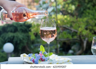 Waiter pouring a glass of cold rose wine, outdoor terrace, sunny day, green garden background