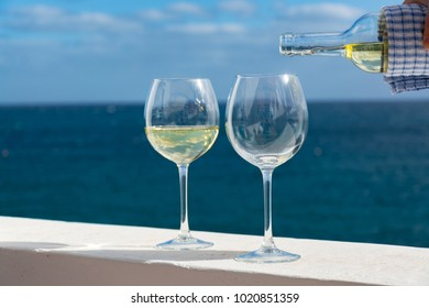 Waiter pouring glass of white wine on outdoor terrace with beautiful romantic  sea view