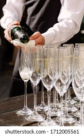 waiter pouring glasses with champagne