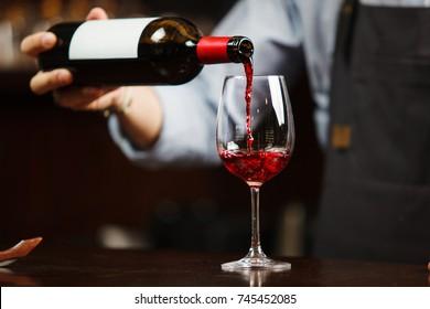 Un garçon verse du vin rouge dans la vigne. Sommelier verse une boisson alcoolisée