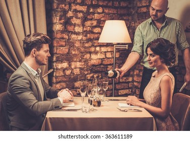 Waiter pouring sparkling wine into glasses to restaurant customers.
