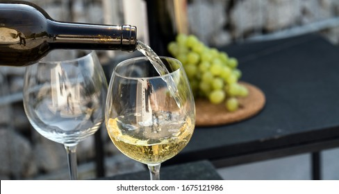 Waiter pouring white wine on outdoor cafe terrace in sunny summer day