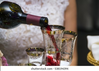 the waiter pours Armenian red wine into the bride's glass during a wedding banquet  Perfect background for a text