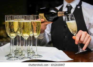 The waiter pours champagne in glasses to guests, beautiful yellow bubbles of champagne