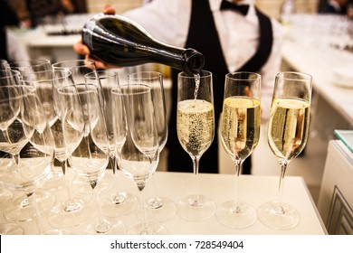 The waiter pours champagne into a glass.Empty glasses on the white table, A row of empty champagne glasses.Furshet, catering.Glasses for champagne or wine.