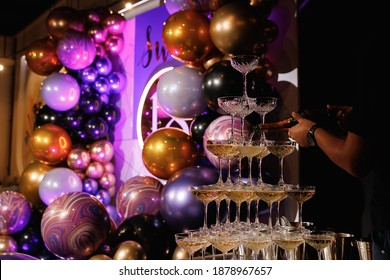 Waiter pours champagne on a slide of glasses. Champagne pyramid for parties at Birthday, party in restaurant. Glasses with champagne in the form of a slide. 2021