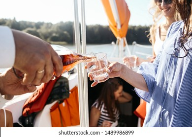 the waiter pours wine in glass on the woman party. Relax concept