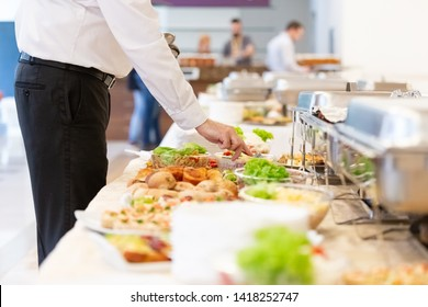 Waiter preparing buffet table with canapes and salads with vegetables.