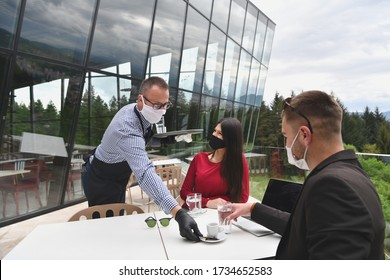 Photo of Waiter with protective medical mask and gloves serving guest with coffee at an outdoor bar café or restaurant new normal concept reopening after quarantine