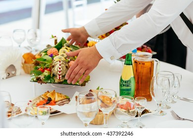 The waiter puts a big dish of fish with vegetables on the table